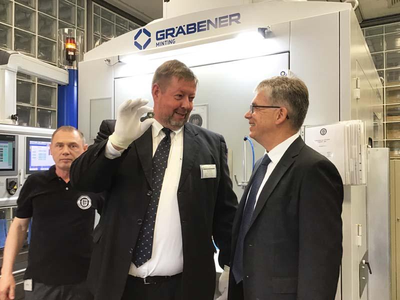 """Markus Floeth und Peter Huber bei der Anprägung der 5-Euro-Münze """"Gemäßigte Zone"""" mit Polymerring"""