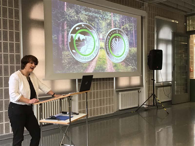 """Baden-Württembergs Staatssekretärin Gisela Splett bei der Anprägung der 5-Euro-Münze """"Gemäßigte Zone"""" mit Polymerring"""
